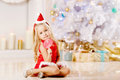 Beautiful little santa girl near the christmas tree happy girl beauty celebrates Stock Images