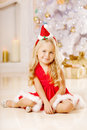 Beautiful little Santa girl near the Christmas tree.  Happy girl Royalty Free Stock Photo