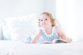 Beautiful little toddler girl with curly hair reading book Royalty Free Stock Photo