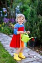 Beautiful little toddler girl in yellow rubber boots and colorful dress watering spring flowers with kids water can Royalty Free Stock Photo