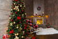 Beautiful living room with rocking chair, decorated modern flaming fireplace and large Christmas tree with a lot of presents Royalty Free Stock Photo