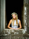 Beautiful lonely fairytale princess waiting at tower window wearing a crown of flowers and for her prince looking out the Royalty Free Stock Photo
