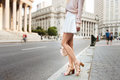 Beautiful long female legs. Beautiful woman standing on city street wearing fashionable summer outfit. Girl on high heels, white Royalty Free Stock Photo