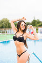 Beautiful long hair tanned female model posing by blue pool water. Outdoor summer portrait of sexy girl in sunglasses Royalty Free Stock Photo