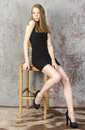 Beautiful long haired young blonde woman with a slender figure in a black mini dress posing Royalty Free Stock Photos
