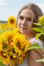Beautiful long haired young woman in the field with sunflowers Stock Images