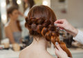 Beautiful, with long, red-haired hairy girl, hairdresser weaves a French braid, close-up in a beauty salon. Royalty Free Stock Photo