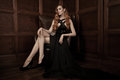 Beautiful luxurious woman sitting on a leather vintage chair