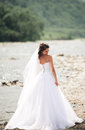 Beautiful luxury young bride in long white wedding dress and veil standing near river with mountains on background Stock Images