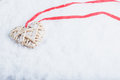 Beautiful magical vintage beige heart tied with a red ribbon on a white snow background. Winter and Christmas concept Royalty Free Stock Photo