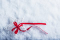 Beautiful magical vintage white star tied with a red ribbon on a white snow background. Winter and Christmas concept. Royalty Free Stock Photo
