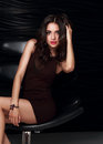 Beautiful makeup brunette model in dress sitting on the armchair Royalty Free Stock Photo