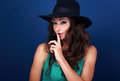 Beautiful makeup female model in hat showing secret sign on blue Royalty Free Stock Photo