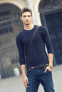 Beautiful man model outdoor with casual outfit in the city center the guy wearing a wear simple long sleeved tight jeans Stock Image