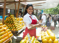 Beautiful mexican saleswoman with oranges on a farmers market Royalty Free Stock Photo