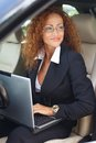 Beautiful middle aged businesswoman redhead in black jacket with laptop behind steering wheel Royalty Free Stock Photos