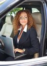 Beautiful middle aged woman redhead businesswoman in black jacket with laptop behind steering wheel Royalty Free Stock Photo