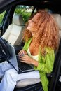 Beautiful middle aged woman redhead with laptop behind steering wheel Stock Photography