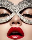 Beautiful Model with Fashion Lips Makeup wearing bright brilliant mask. Masquerade style woman. Holiday celebration look Royalty Free Stock Photo