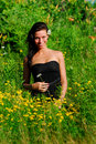 Beautiful model in a field holding a flower Royalty Free Stock Image