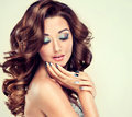 Beautiful model with long curly hair fashion makeup and silver nails Royalty Free Stock Photo