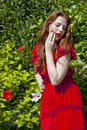 Beautiful model white skin wearing red dress green foliage background Stock Image