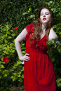 Beautiful model white skin wearing red dress green foliage background Stock Photo