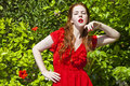 Beautiful model with white skin wearing a red dress with green foliage in background Royalty Free Stock Photos
