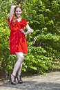 Beautiful model with white skin wearing a red dress with green foliage in background Stock Photography