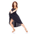 Beautiful modern dancer in a full skirted black dress and high heels holding a pose with her skirt raised on a white background Stock Photography