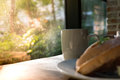 Beautiful morning with a  white cup of coffee with blurred waffle on wooden table Royalty Free Stock Photo