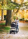 Beautiful mother with baby carriage walking in autumn park. Royalty Free Stock Photo