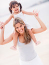 Beautiful mother carrying her daughter shoulders beach Royalty Free Stock Image