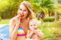 Beautiful mother and child in the open air nature beauty mothe her baby eat fruit together outdoor portrait of a happy Stock Images