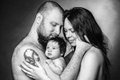 Beautiful mother and father smiling holding their newborn baby girl. Royalty Free Stock Photo