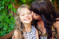 Beautiful mother kisses cute little daughter Stock Photo