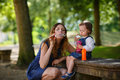 Beautiful mother and little daughter blowing soap bubbles in sum together summer park Stock Photos