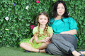 Beautiful mother and little girl sit on grass in garden next to verdant fence Stock Photo