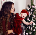 Beautiful mother with luxurious dark hair posing with her cute little girl beside Christmas tree