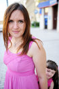 Beautiful mother in pink dress posing outdoors Royalty Free Stock Image