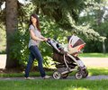 Beautiful mother pushing baby carriage in park full length of young Royalty Free Stock Photos