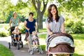 Beautiful mother pushing baby stroller in park portrait of with friends and children background Royalty Free Stock Images