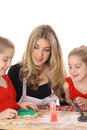 Beautiful mother and twin daughters decorating coo Stock Photography