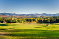 Beautiful Mountain Landscape at Sunset with a Golf Course in Foreground Royalty Free Stock Photo
