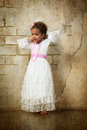 Beautiful mulatto girl in white dress on wall background Royalty Free Stock Images