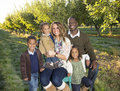 Beautiful multi ethnic family portrait outdoors a smiling happy with three children Stock Photo