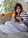 Beautiful multiracial woman reading with cat Stock Images