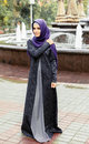 Beautiful Muslim woman in the modern Islamic dress walk in a city park Royalty Free Stock Photo