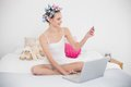Beautiful natural brown haired woman in hair curlers shopping online with a laptop bright bedroom Stock Image