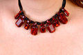 Beautiful necklace a closeup picture of a burgundy around the neck of a woman Royalty Free Stock Photos